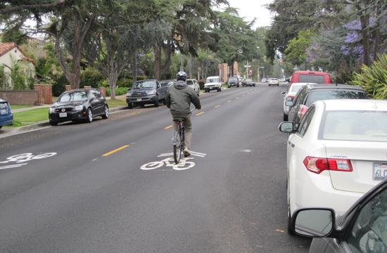 A bicycle rider passes over one of the newly marked Sharrows (indicating for drivers to share the roads) on 14th Street in Santa Monica.