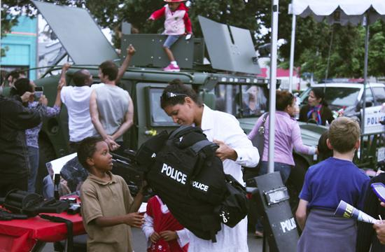 A mother helps her son try on Santa Monica Police Department SWAT armor at one of the many stations set up by the police to interact with the public they serve at the local National Night Out Block Party.