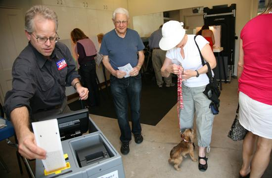 Poll inspector David Mayhan assists voters at a polling station at a private home