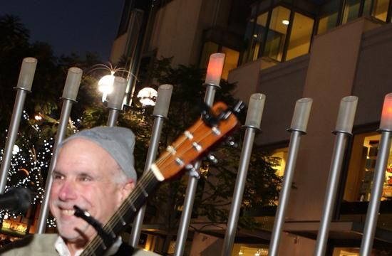 Rabbi Neil Comess-Daniels of Beth Shir Shalom Temple celebrates with song after lighting the first Chanukah candle on the Menorah at the 3rd Street Promenade ceremony. Celebrated by congregation members and guests