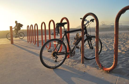 A bike on a bicycle rack on along the bike path with the Santa Monica Pier seen in the background.