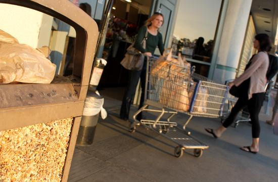 Shoppers seen outside a Santa Monica Albertsons. A single-use plastic bag can be seen in the garbage bin in the foreground
