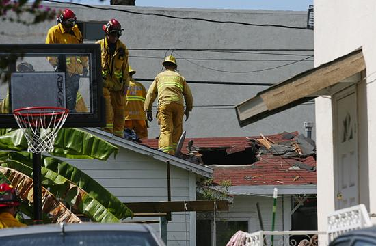 A gaping hole is apparent in the roof of a home on the 1400 block of 17th Street near Broadway