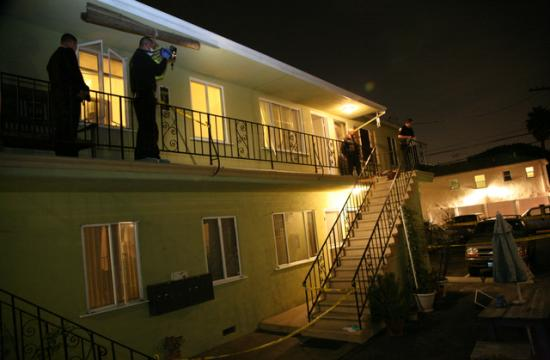 Officers of the Santa Monica Police Department document the area outside an apartment that was crime scene where a man brutally stabbed his former girlfriend multiple time before being shot and killed by police on April 13