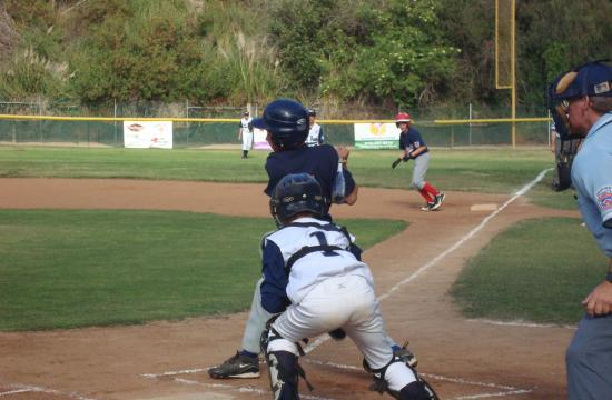 Santa Monica Little League's Alex Rubinek swings to advance Aiden Cullen to second base in the first game of the District 25 All-Star Tournament on Friday.