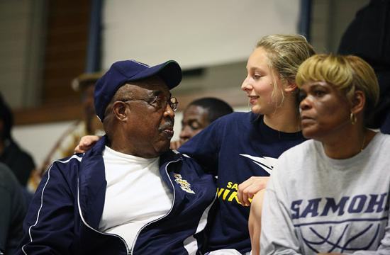 A former student talks to retired softball coach John Heaven while he was attending a varsity boys basketball playoff in January 2011.