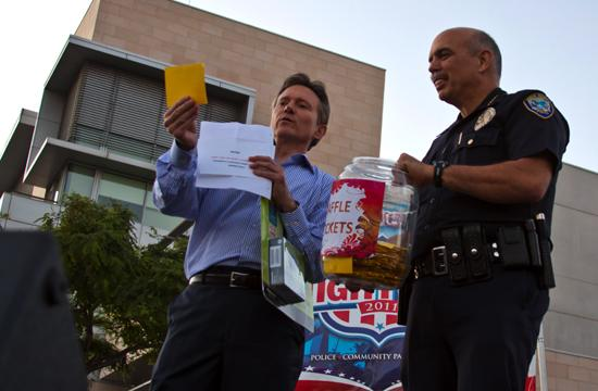 Santa Monica Police Chief Timothy Jackman clutches the raffle jar while KTTV journalist Jeff Michael announces the winner of a Panasonic Lumix S3 camera during the SMPD's block party on Tuesday