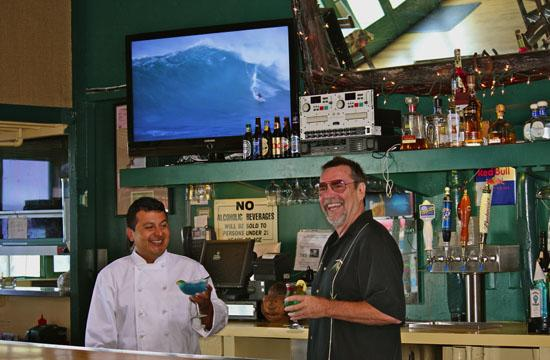 """Russell """"Rusty"""" Barnard (right) hangs out behind the bar during the relaxing daylight hours sharing a fun moment with culinary expert Chef Carlos"""