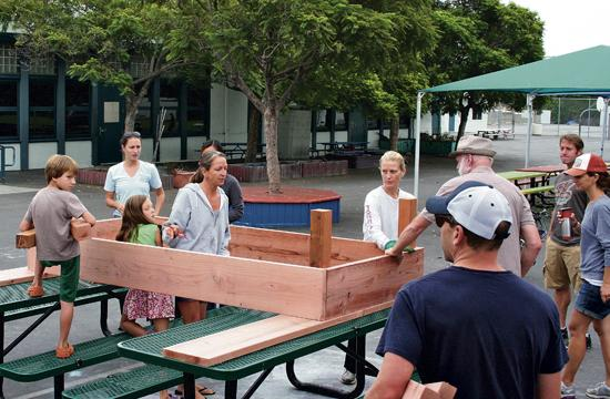 Parents and students build one of the plant boxes for the garden.