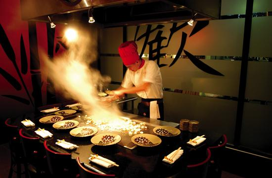 One of Benihana's chefs puts on a show as he serves customers a piping hot meal.