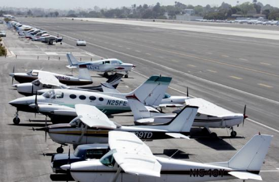 Propeller engine planes sit just off the runway at Santa Monica Airport.