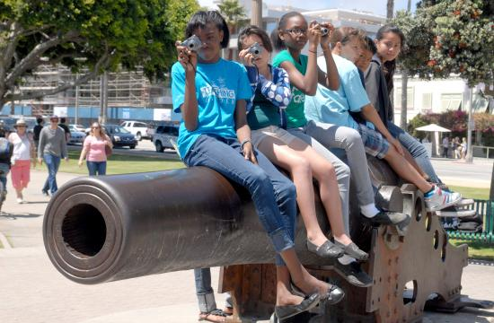 Children snap photos while sitting on the historic cannon at Palisades Park during one of the 'Kids with Cameras' workshops this summer.