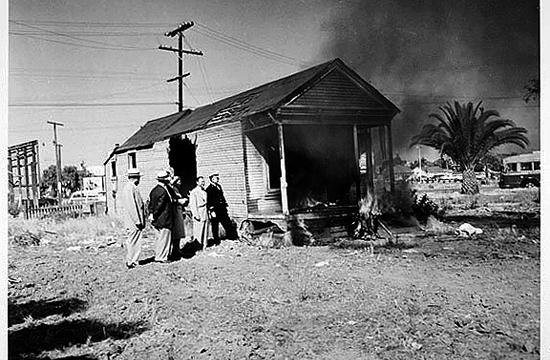 Officials watch as a house burns in the Belmar Triangle neighborhood in the 1950s to make way for the Civic Auditorium.