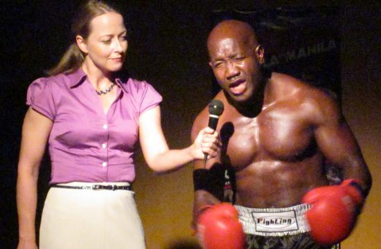 """Undisputed light-heavyweight Champion Likanjo """"The Nightmare"""" Omakada (Theodore Mark Martinez) in pre-fight interview with a reporter (Sharon Elliott) expressing his disdain for """"The Peoples Champ"""" number one contender Micheal """"Too Quick"""" Taylor."""