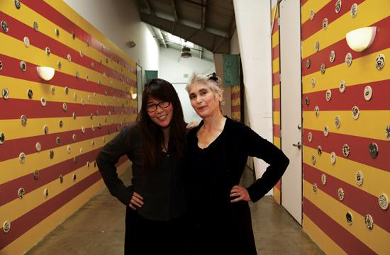 """The Santa Monica Museum of Art is currently exhibiting its most extensive educational public art program called """"WallWorks: The Walls Have Eyes."""" Pictured is SMMoA Director of Education Asuka Hisa (left) and Executive Director Elsa Longhauser."""