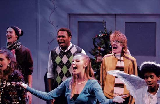 Kelly Derouin (in blue sweater) who plays Mrs. Scrooge shows her revitalized Christmas spirit.