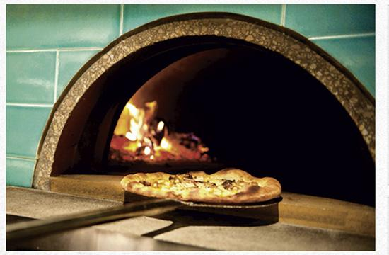 The pizza oven at Milo and Olive cooks a legion of savory pizzas such as pork belly sausage