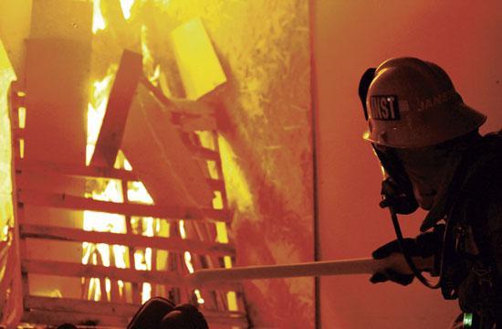 Captain Josh Janssen of the Riverside County Fire Department lights the fire inside the training building on the 1600 block of Colorado in Santa Monica on Sunday. The charred structure will now be demolished to make way for the Expo Light Rail Line.