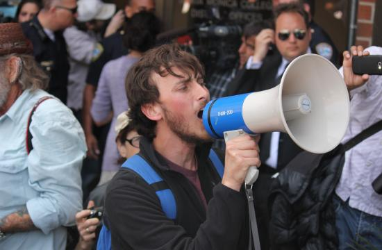 Speaker Michael Pronilover of the Student Organizing Committee led Thursday's march in protest of SMC's approved two-tier plan.