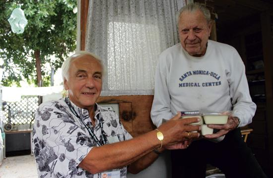 Volunteer Lars Jensen (left) delivers a meal to a Meals On Wheels West client. The organization is urgently looking for a new meal supplier.