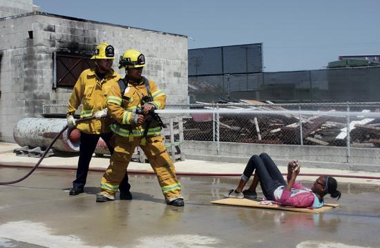 Two firemen demonstrate how to use a fire hose at the Fire Academy Wednesday as a Kids with Cameras participant gets in position for the perfect shot.