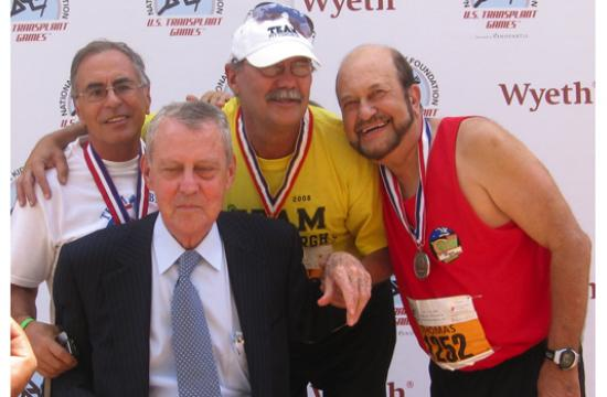 Tom Elias (far right) receives his long jump medal from Dr. Thomas Starzl at the 2008 Transplant Games of America.