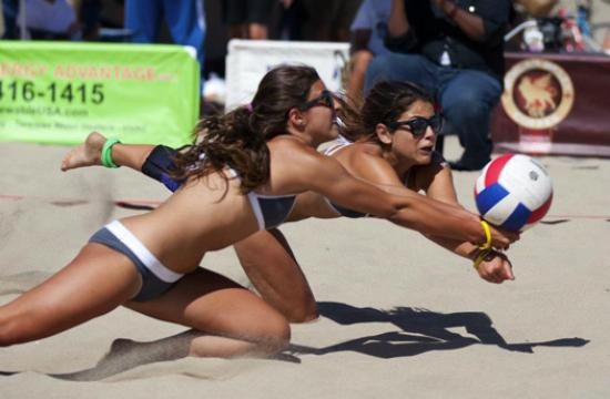 Natalie Anselmo (left) and Olivia Zelon digging a ball during their Volleyball Championship win last weekend.