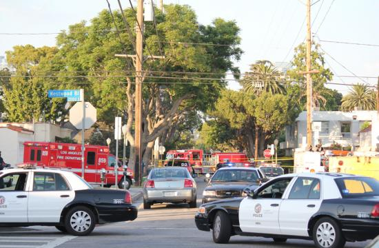 Police cars and firetrucks block the road along Mississippi Ave. and Westwood Blvd. in West Los Angeles after a small plane crashed in the neighborhood.