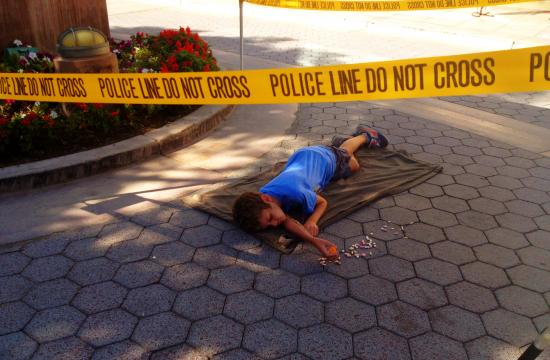 Bright caution tape encircled the child who lay on the ground