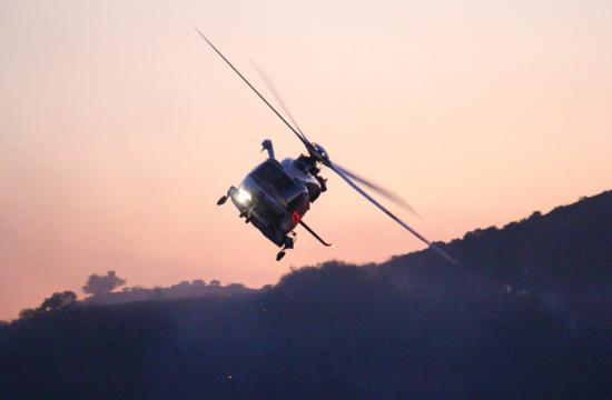 A Los Angeles County Fire Department helicopter circles around the hills of Bel Air after dropping water on the pockets of fire below just after sunset on Friday