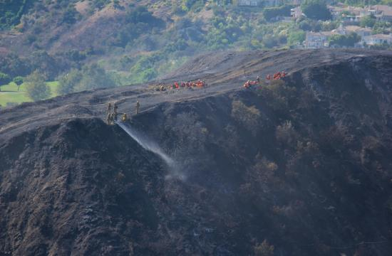 Los Angeles City fire crews hose down the Bel Air mountainside in order to prevent any hot spots from re-igniting in the 100+ degree temperatures affecting Los Angeles Saturday afternoon Sept. 15