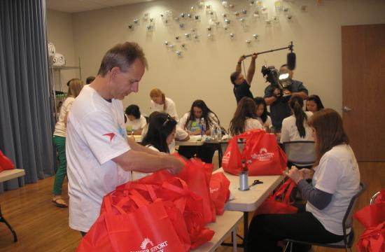 Agensys employees prepare gift bags for underinsured Latina breast cancer survivors who will be participating in an upcoming Regresar al Bienestar workshop. A total of 29 Agensys employees took part in the project.