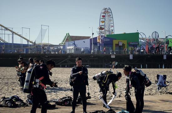 Scuba divers gear up before collecting trash in the ocean around the Santa Monica Pier as part of Coastal Cleanup Day.
