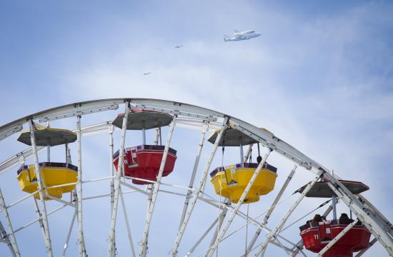The space shuttle Endeavour flies over the Ferris wheel at Pacific Park on the Santa Monica Pier.