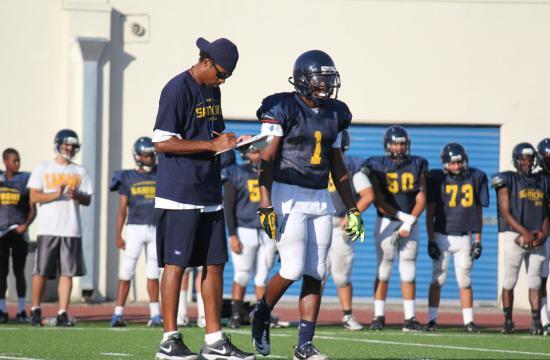 Santa Monica High School's Sebastian LaRue walks with Head Coach Travis Clark during football practice at Santa Monica High School earlier in the season.