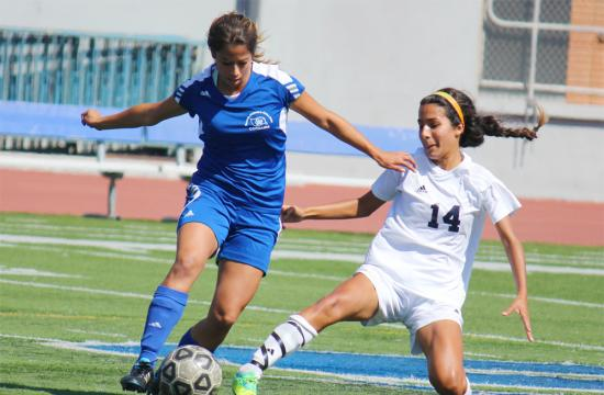 Midfielder Yennifer Baca of Santa Monica College works to get the ball around Citrus College's Leandra Escobar during the first half.