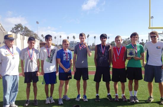 Volunteer Cross Country Coach Pat Cady (far left) poses with the Vikings Boys Cross Country team after they won the Boys Varsity three miles at the Mt. SAC Invitational Saturday