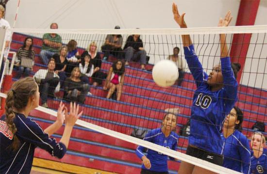 Windward's Asha Walker blocks a kill by Crossroads Nina Ferguson in the first set to put Windward up 22-7 Tuesday afternoon at Crossroads High School.