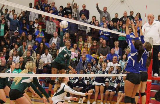 Archer's Lauryn Brame goes up for a kill against the defense of Pacifica Christian's Shannon Volpis (left blocker) and Maile Lane (right blocker) during the second set at Crossroads High School Saturday night.  The Seawolves large crowd cheers on the defense of the Seawolves as they attempt to stop an Archer comeback that could have cost the Seawolves the game.