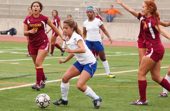 Santa Monica College forward Daysi Serrano (center) makes a move against the defense of Pasadena City College in the first round of the playoffs at Occidental College Thursday afternoon.  Serrano scored the first goal in the game for the Corsairs.