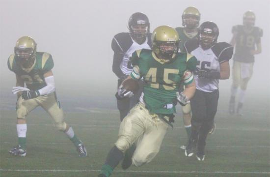 St. Monica running back Kevin Holubowski gains yardage in the CIF Semi-Finals against the defense of Rio Hondo Prep during the second quarter at home Friday night.  Holubowski rushed for 139 yards in the game.