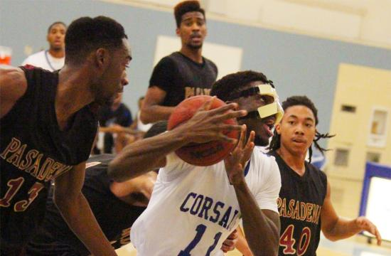 Santa Monica College forward David Nwaba fights off a grip of Pasadena City College defenders during the second quarter at home Friday