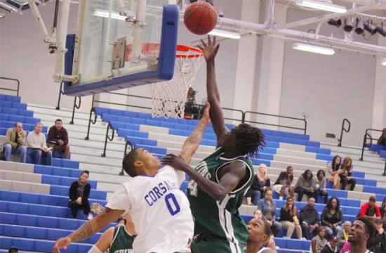 Griffins guard Todd Turner scores a basket over SMC's DeAndre Henderson in the third quarter during the SMC Tournament at home Saturday afternoon.