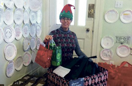 MOWW President/CEO RoseMary Regalbuto plays elf while she prepares gifts for distribution to home bound clients in Santa Monica.