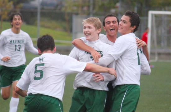 St. Monica High School forward Jack Cain (center) is congratulated by his teammates after kicking the winning goal against St. Paul at home Friday afternoon.  Cain had three goals in the game.
