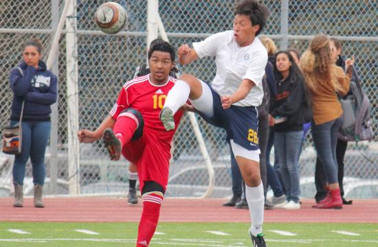 Santa Monica High School's Dylan Torres (right) jumps for the ball with Hawthorne's Candelario Paz (left) at home Thursday