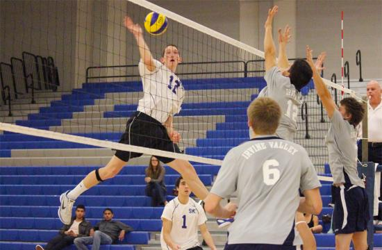 Santa Monica College middle blocker Jason Mallek goes up for a kill against the defense of Irvine Valley College during the second set at home Friday night.