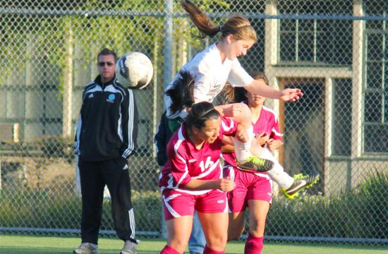 St. Monica soccer forward Sasha Meyer (center) jumps for the ball against the defense of University Prep in the quarterfinals of the CIF Playoffs at Airport Park Thursday afternoon. St. Monica lost the game in an intense shootout 5-4 after the game was tied 1-1 after double overtime.