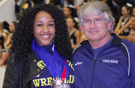 Samohi Wrestler Jessica Walker and Samohi Wrestling Coach Mark Black smile at an award ceremony for Walker during halftime at the Santa Monica High School Boys Basketball Semi-Finals game Tuesday night.  Walker won the California State Wrestling Championship Title for the second year in a row Saturday night.