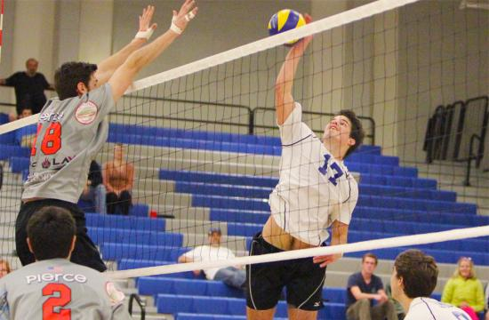 Santa Monica College outside hitter Charlie Schmittdiel goes up against Evan Bender of Pierce College late in the third set at home Friday night.